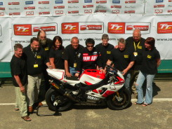 Members of a winning TT racers' team pose for their victory shot