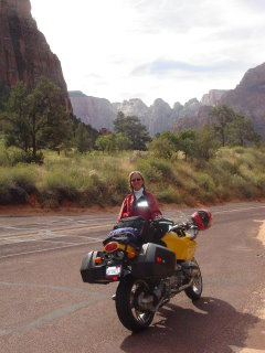 A motorcycle posing by a really big rock, somewhere in Utah