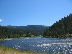 A rolling river parallels the road while motorcycling in Idaho.