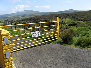 A fence blocking a small country road from movement of horses and cows.