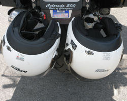 Two helmets locked together on the back of a bike