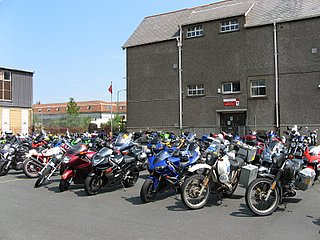 Many bikes parked in a field at a rally