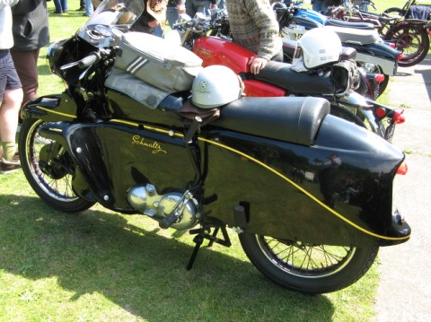 A great vintage motorcycle at an outdoor rally.