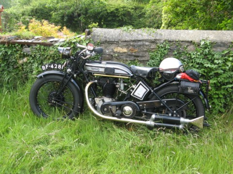 A beautiful vintage motorcycle, parked in a yard in the UK